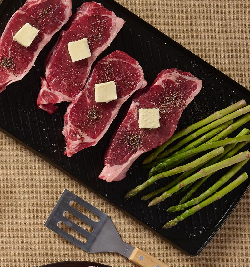 overhead photo of wellsley farms steaks on a grill pan with butter and asaparagus, on a burlap background with a spatula in the frame