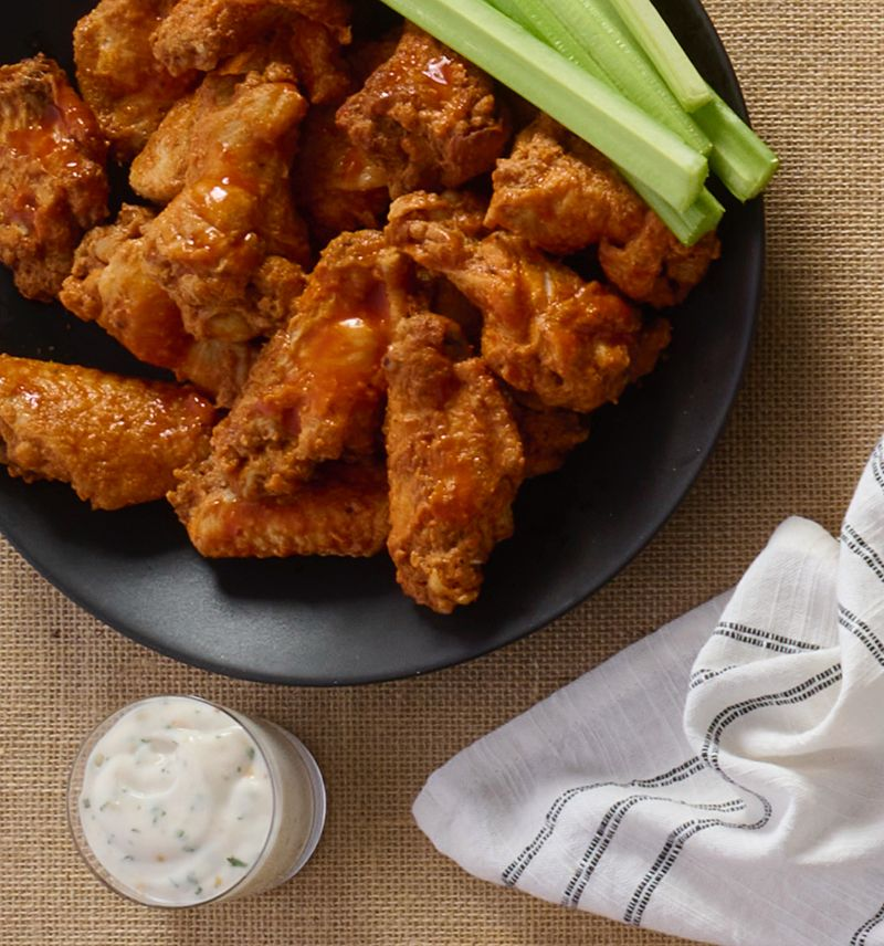photo of wellsley farms cooked buffalo wings garnished with celery and a saucer of ranch, on burlap