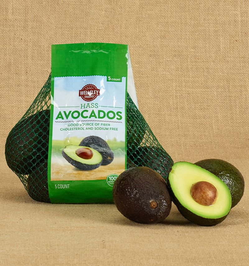 Produce product photo featuring a bag of wellsley farms avocados with a fresh cut open avocado next to it, on a burlap background